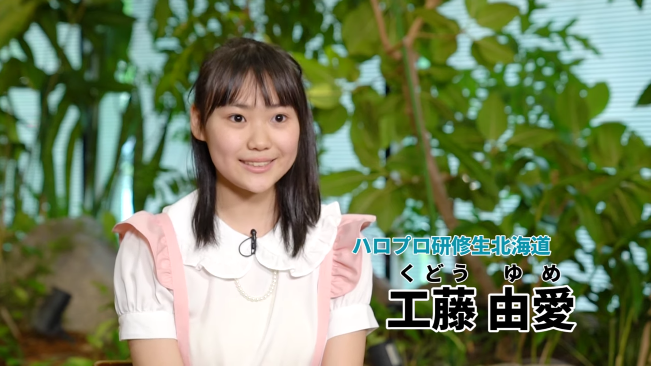 A girl in a white blouse (Yume) with a pink-trimmed pink pinafore is sitting calmly. Text (in Japanese): Hello Pro Kenshuusei Hokkaido - Kudo Yume