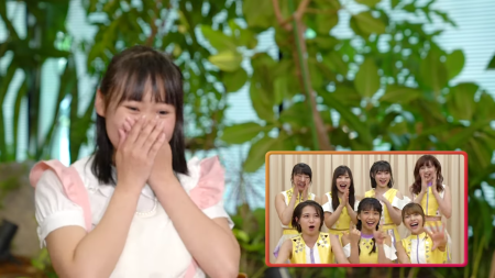 A girl in a white blouse (Yume) with a pink-trimmed pink pinafore covering her mouth with her hands in surprise. In the left corner is a shot of Juice=Juice in a variety of expressions as they welcome her to their band. Plants and blinds can be seen in the background.