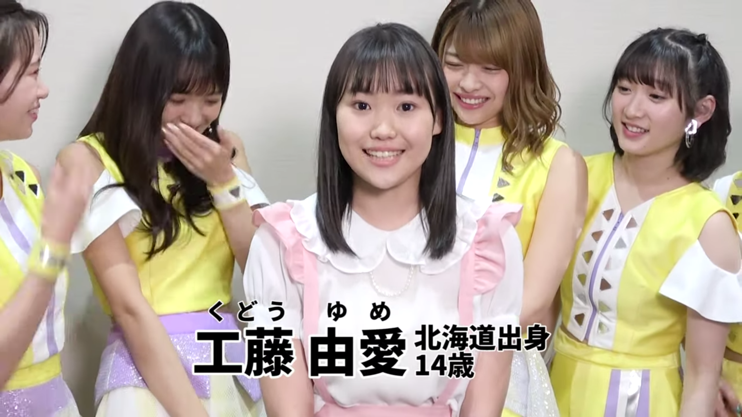 A girl in a white blouse (Yume) with a pink-trimmed pink pinafore is standing in front of four women in yellow and white costumes (Juice=Juice members Takagi Sayuki, Inaba Manaka, Kanazawa Tomoko, Miyamoto Karin). Text (in Japanese): Kudo Yume - From Hokkaido - 14 Years Old.