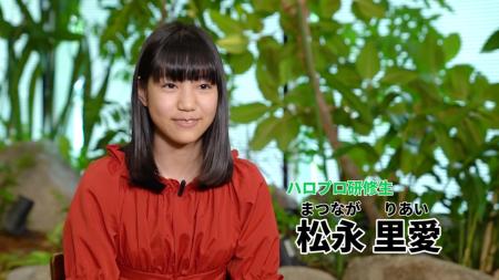 A girl in a red blouse (Riai) is sitting calmly. Text (in Japanese): Hello Pro Kenshuusei - Matsunaga Riai.