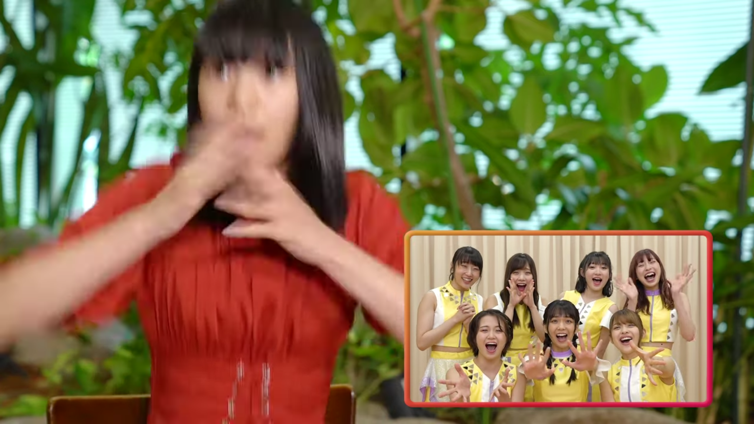 A girl in a red blouse (Riai) jumps up in surprise. The image is caught mid-motion so she is somewhat blurred. In the left corner is a shot of Juice=Juice in a variety of expressions as they welcome her to their band. Plants and blinds can be seen in the background.