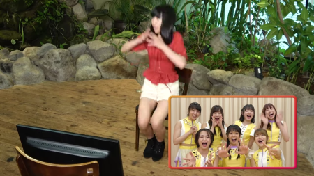 """A girl in a red blouse and white shorts (Riai) jumps up in surprise. The image is caught mid-motion so she is somewhat blurred. In the left corner is a shot of Juice=Juice in a variety of expressions as they welcome her to their band. Plants, the """"rock wall"""" bordering them, the floor, and a television screen can be seen in the background. (Alternate shot of the previous scene.)"""