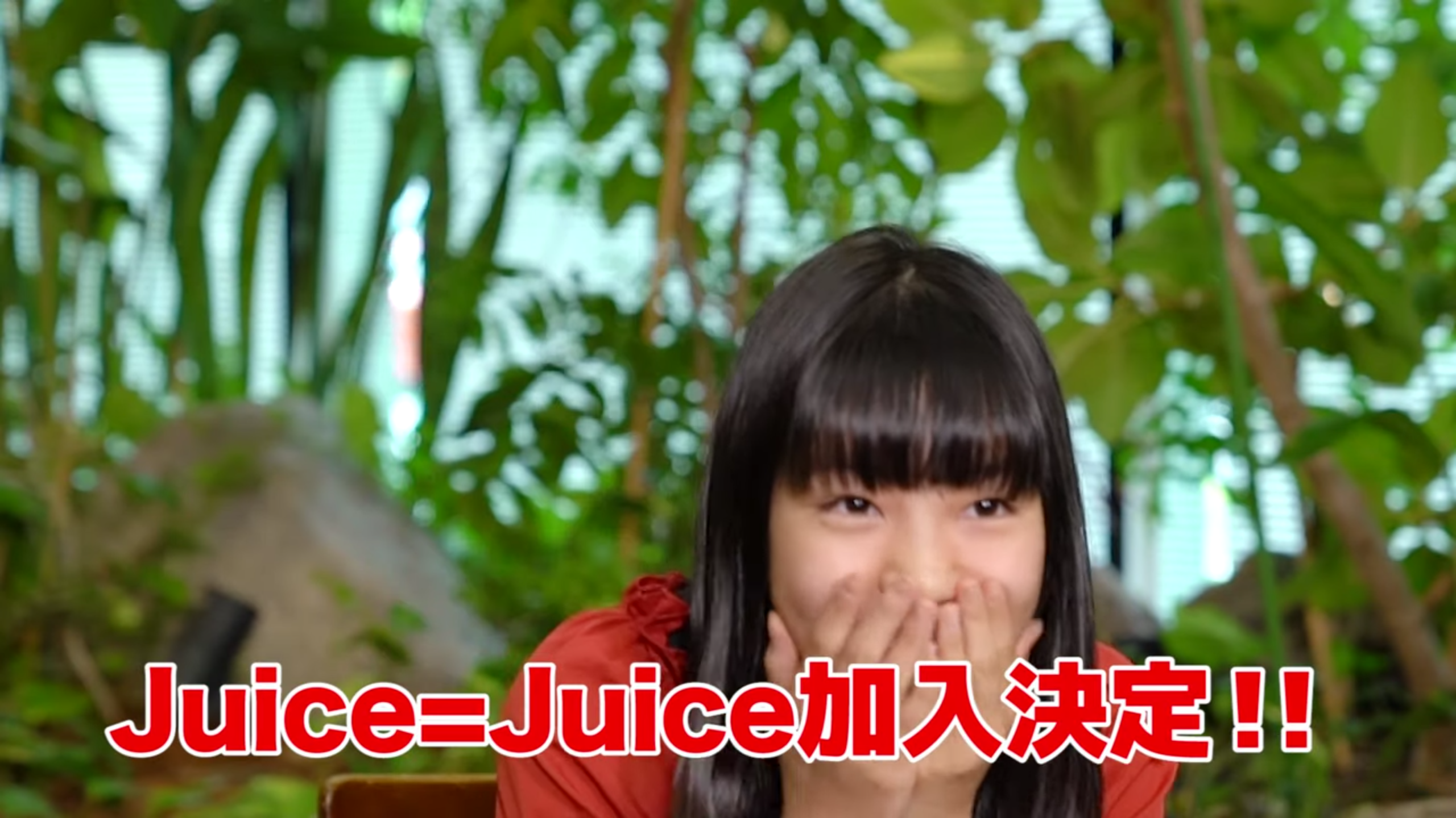 A girl in a red blouse and white shorts (Riai) holds her mouth in her hands in surprise. Text (in Japanese): Juice=Juice Addition Decision!!