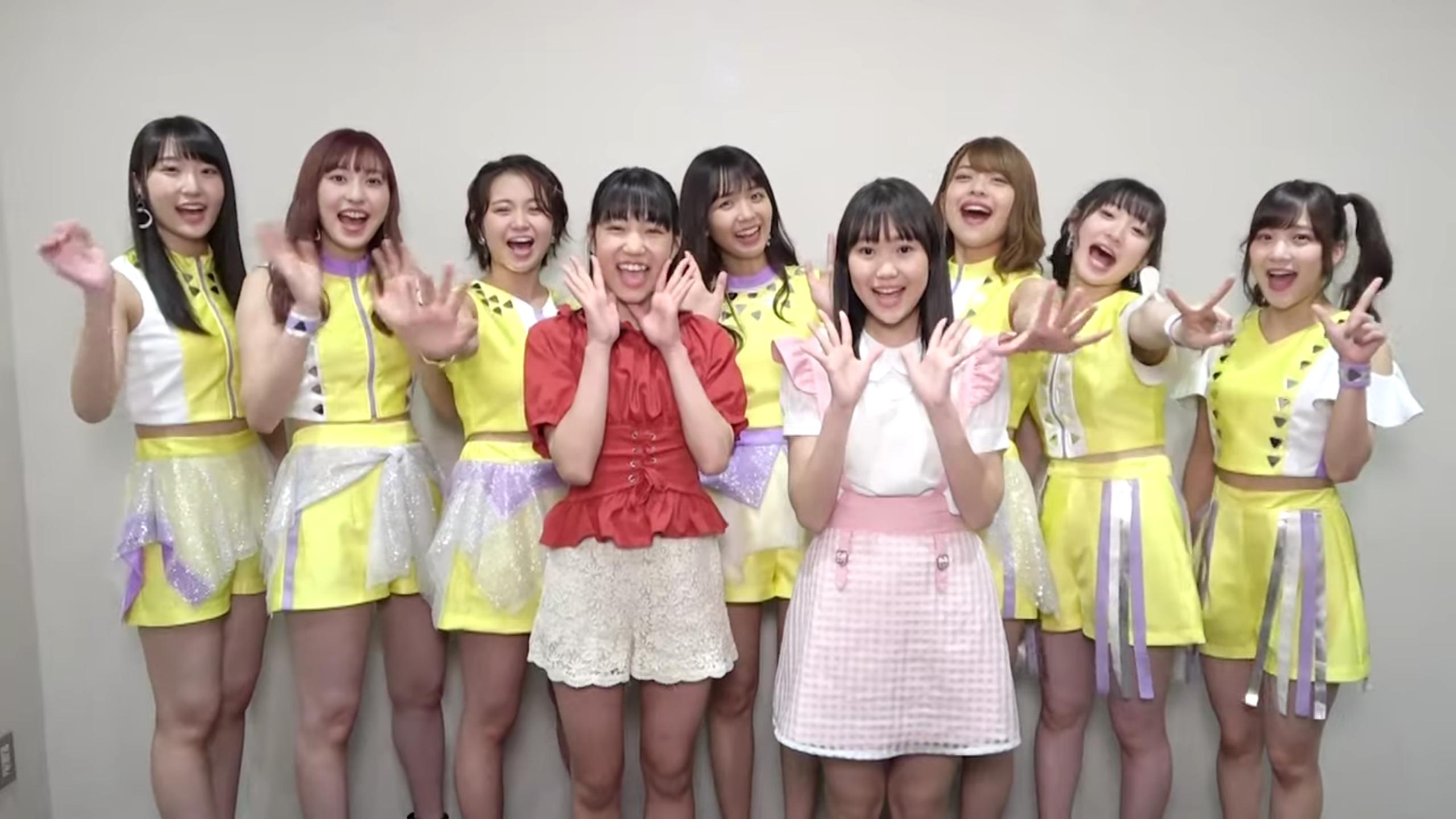 Seven girls/women in predominantly yellow costumes (Juice=Juice), Matsunaga Riai, and Kudo Yume all wave goodbye. Matsunaga and Kudo are standing in front of their new groupmates.
